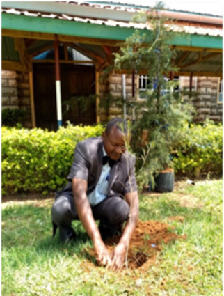 Elder Obadiah planting a tree at Githungari church.  40 trees were planted on the church grounds.